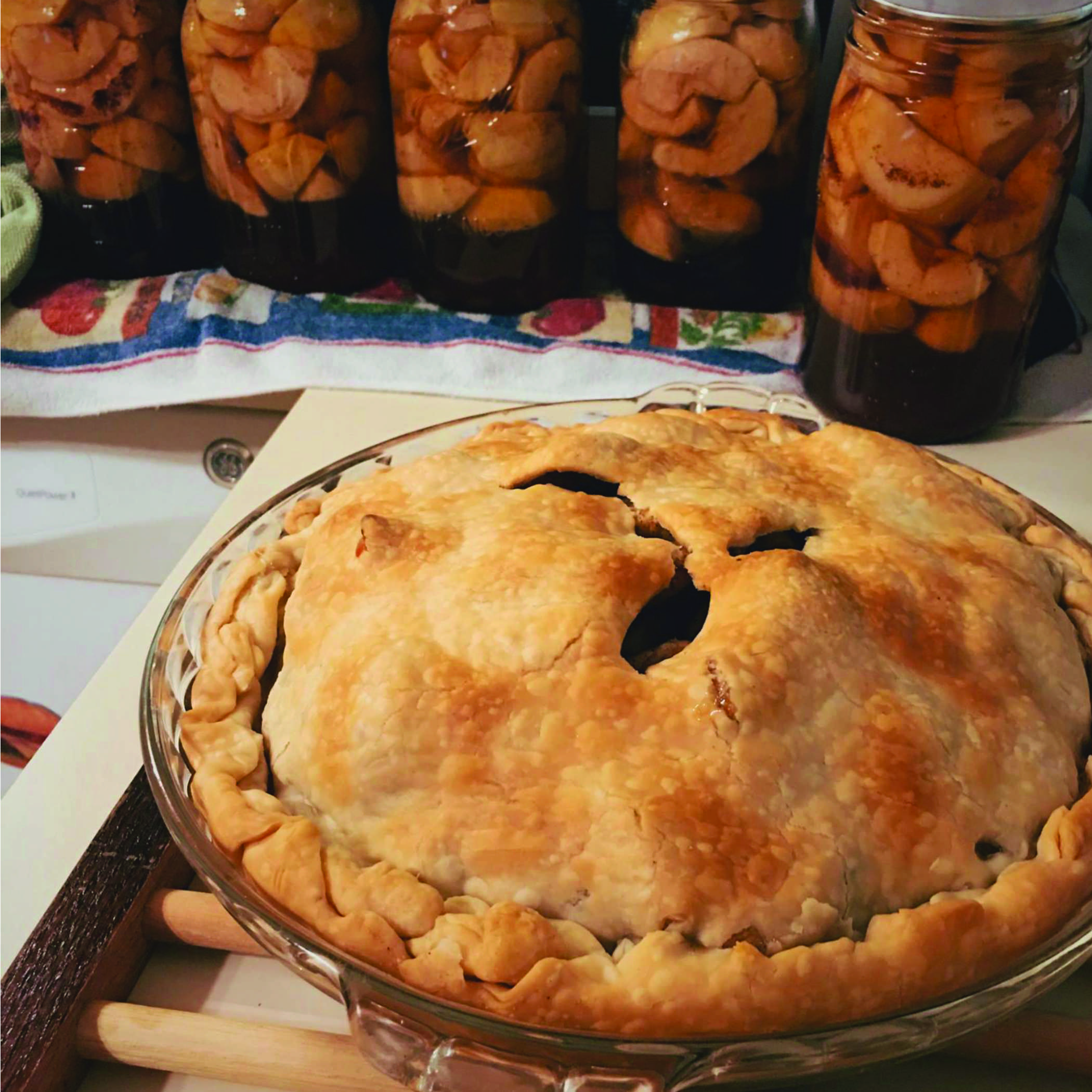 an apple pie and jars of apple slices cooling on a counter top