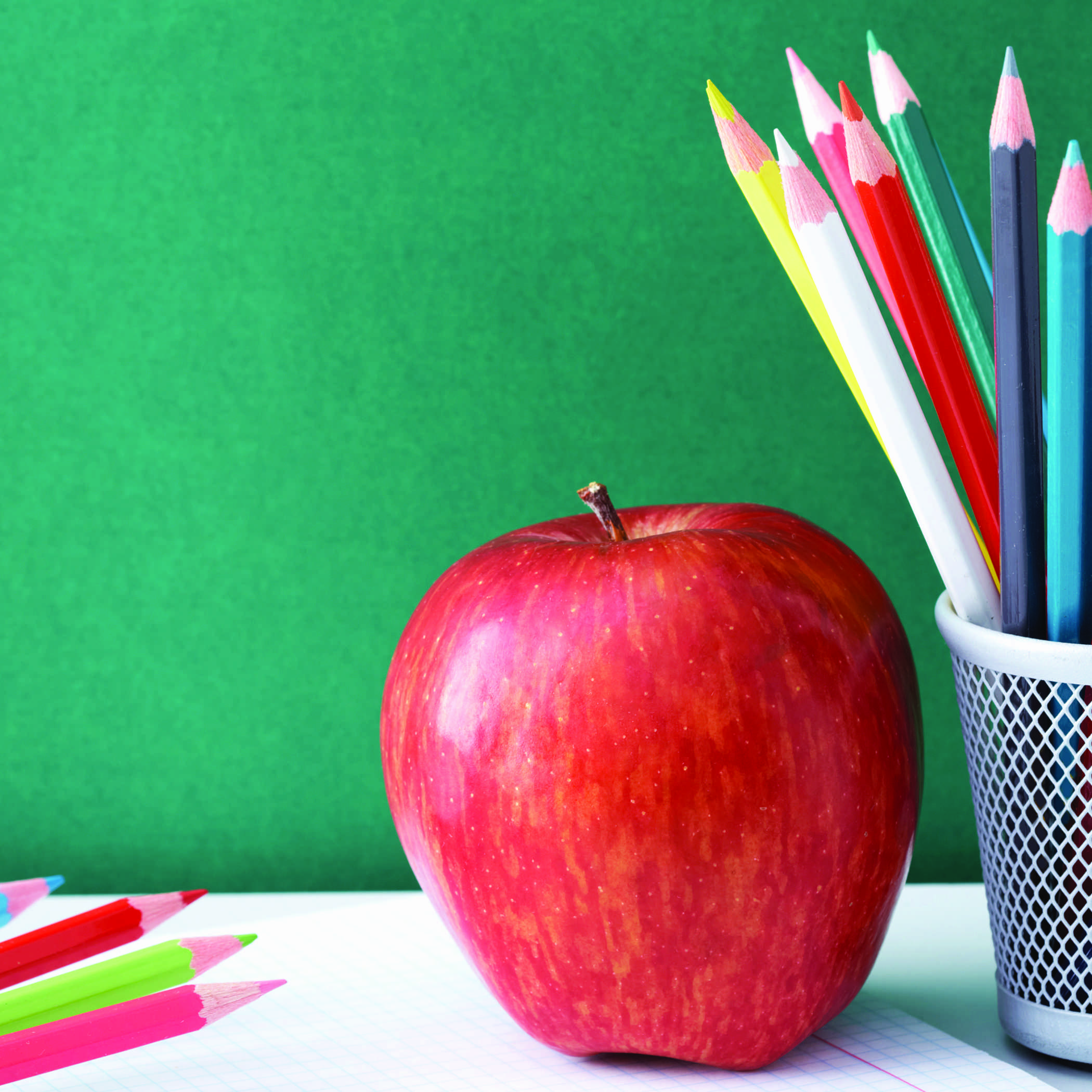 a red apple and a cup of colored pencils on a desk