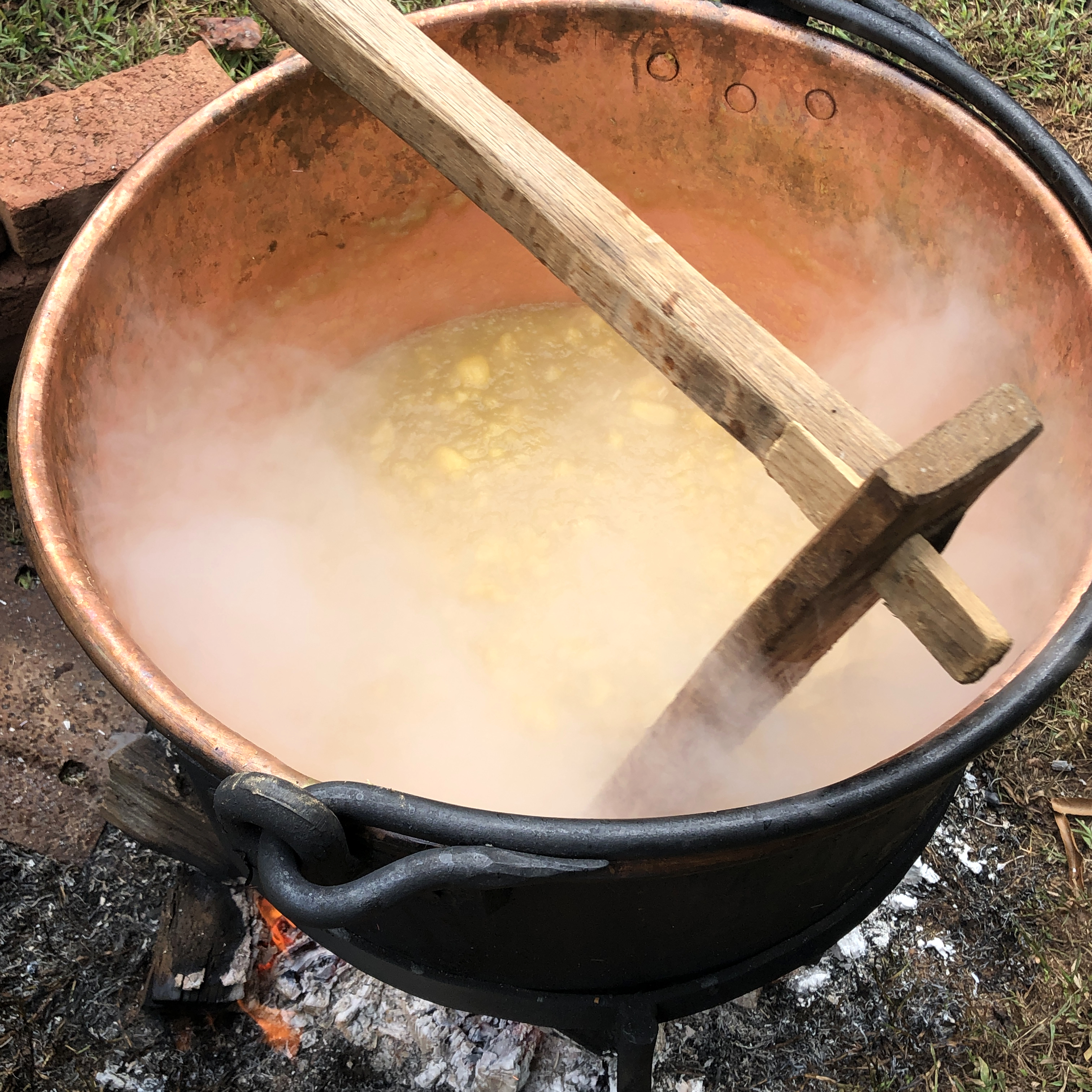 a large copper cauldron filled with apple butter being stirred with a wooden paddle