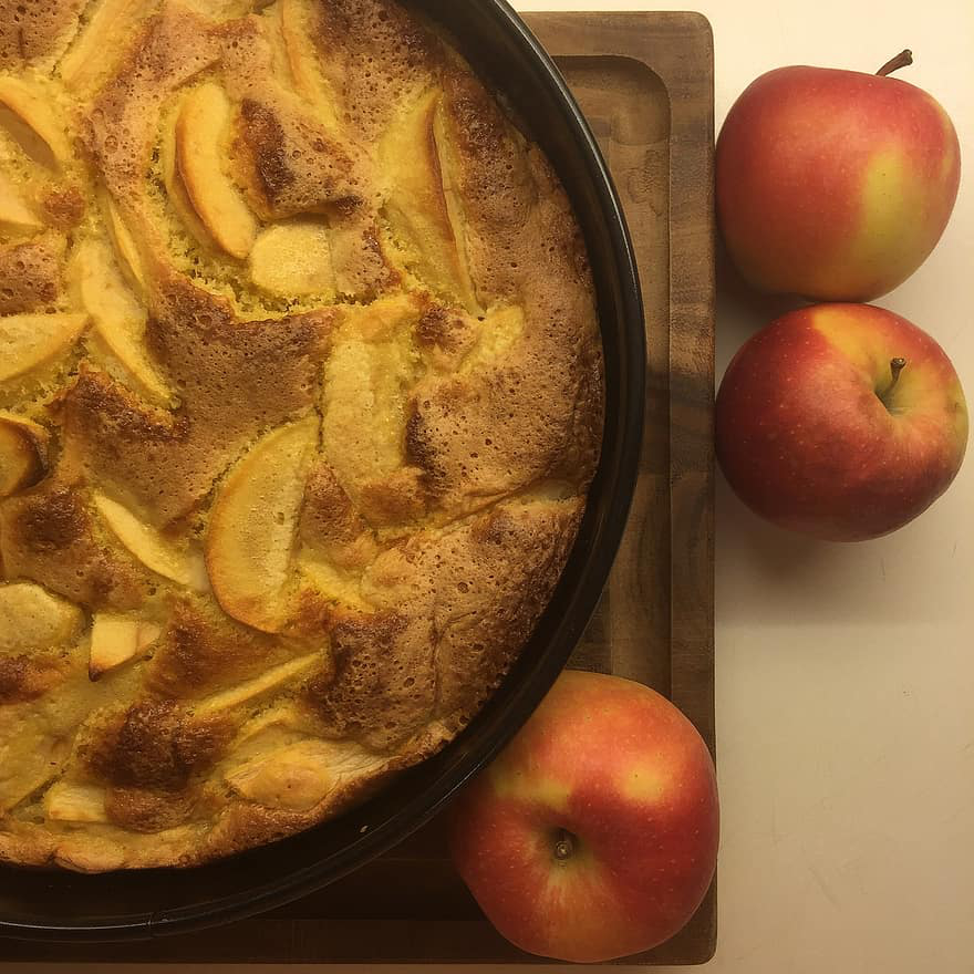 an apple cobbler and three red apples
