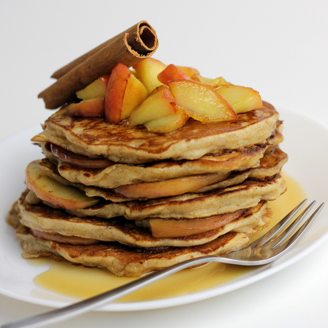 a stack of pancakes with apples and a cinnamon stick on top