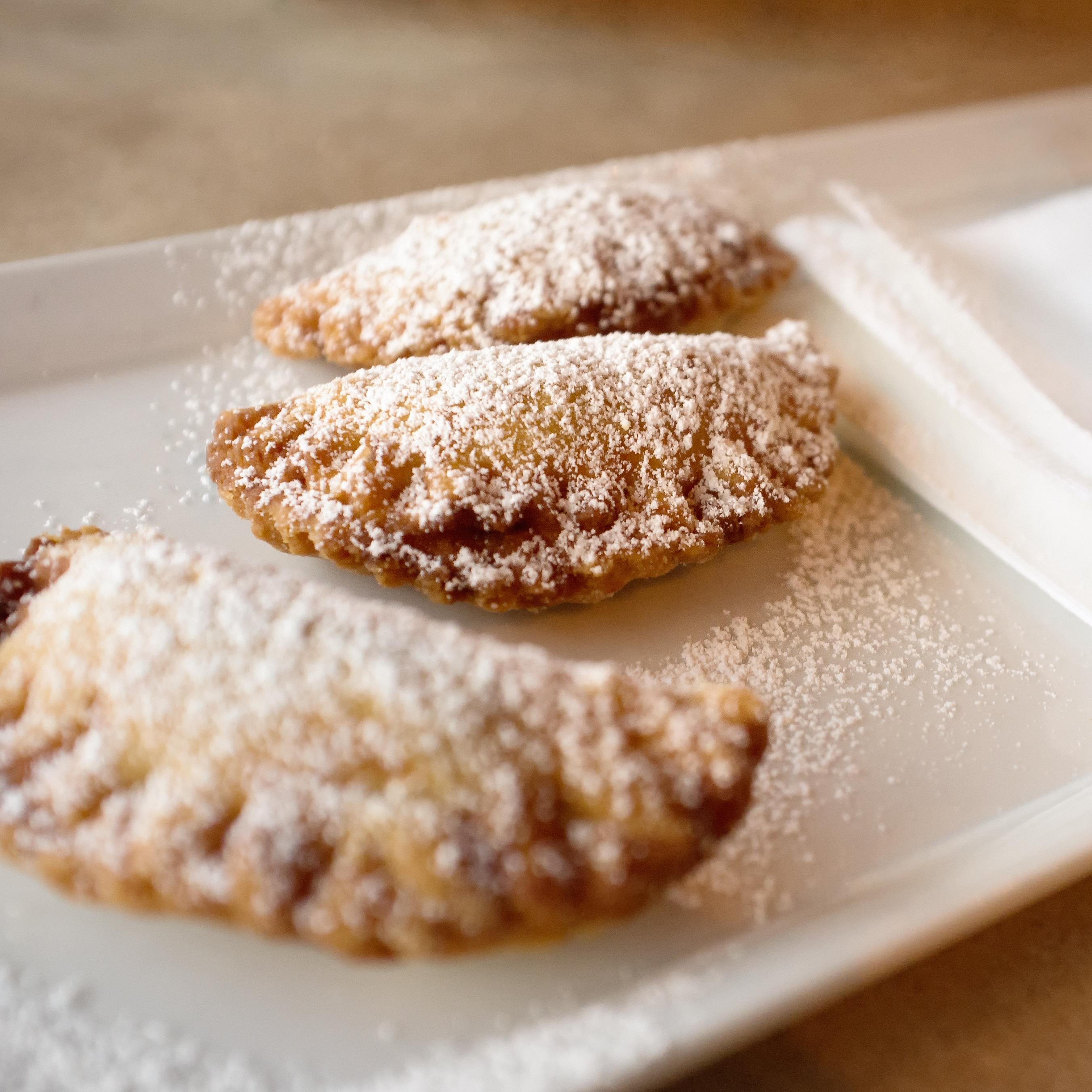 three half circle fried pies sprinkled with powdered sugar