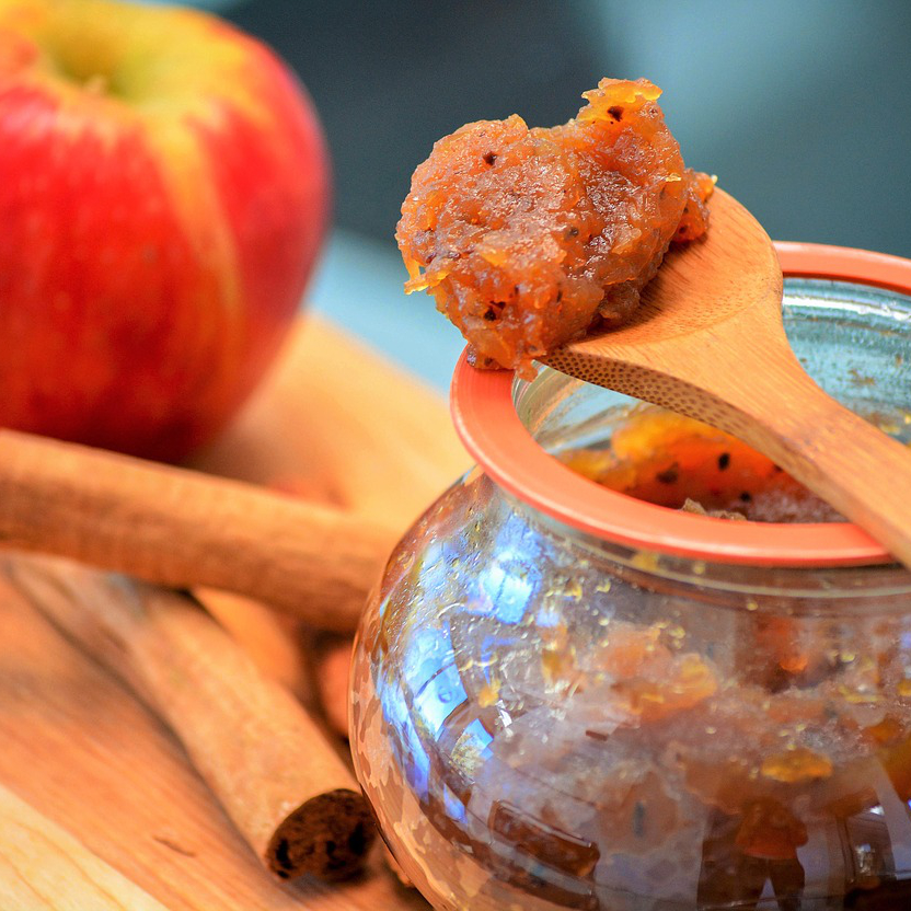 apple butter in a jar with a wooden spoonful of apple butter sitting on top of the jar