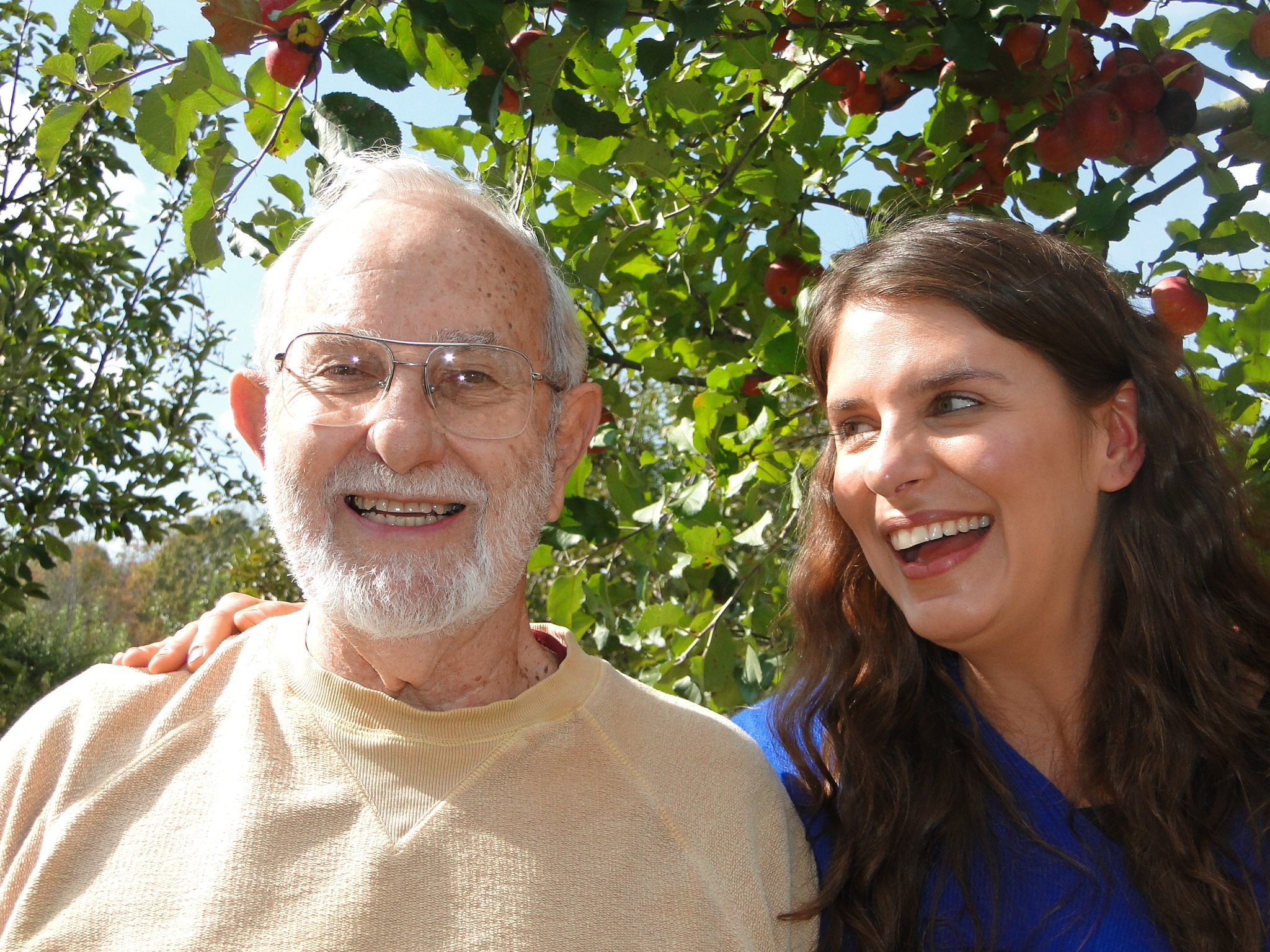 Lee Calhoun, with white hair and beard, standing next to Vivian Howard who has long brown hair. Vivian is looking and smiling at Lee