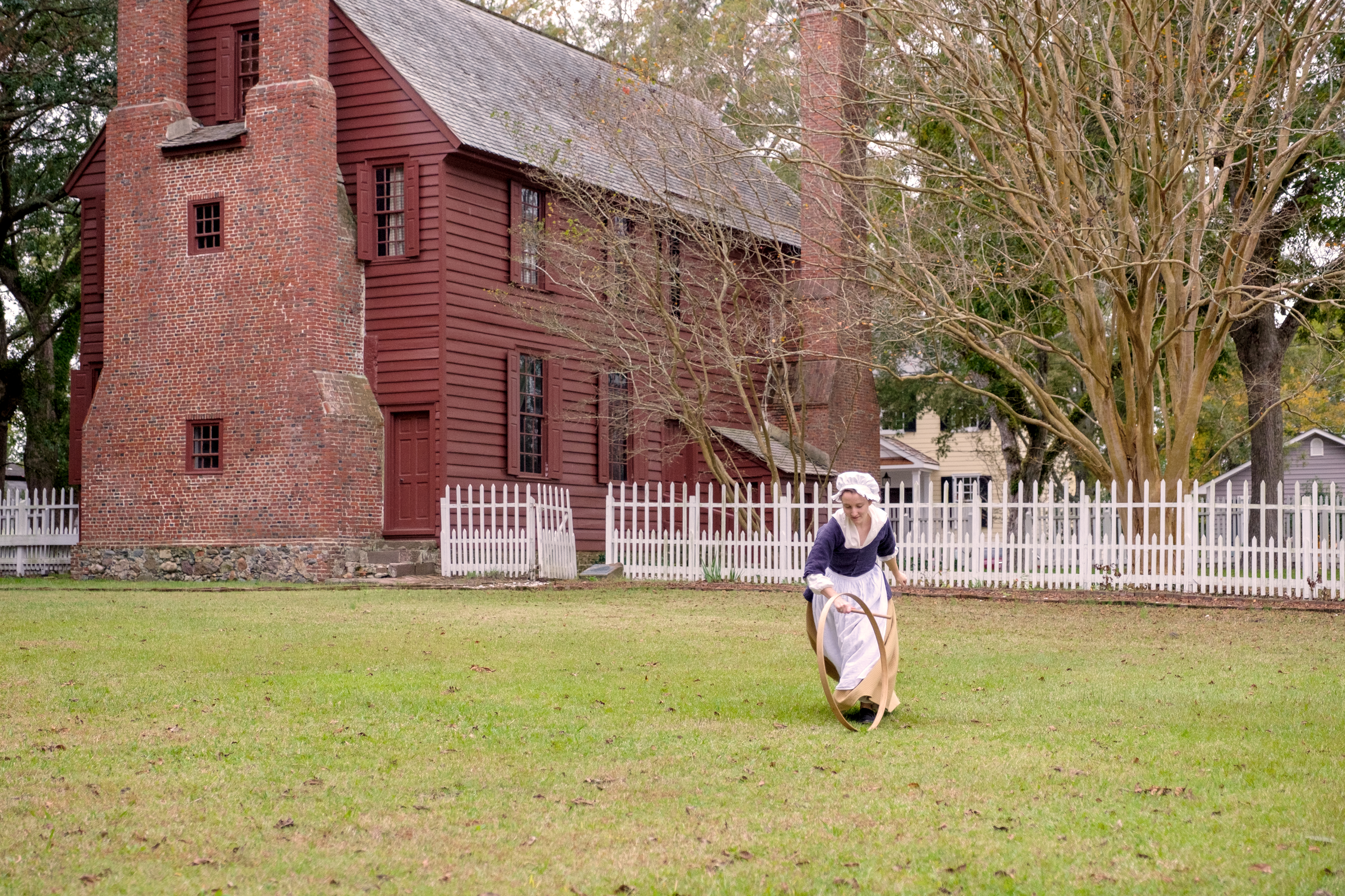 A girl dressed in costume playing hoops in front of a historic house