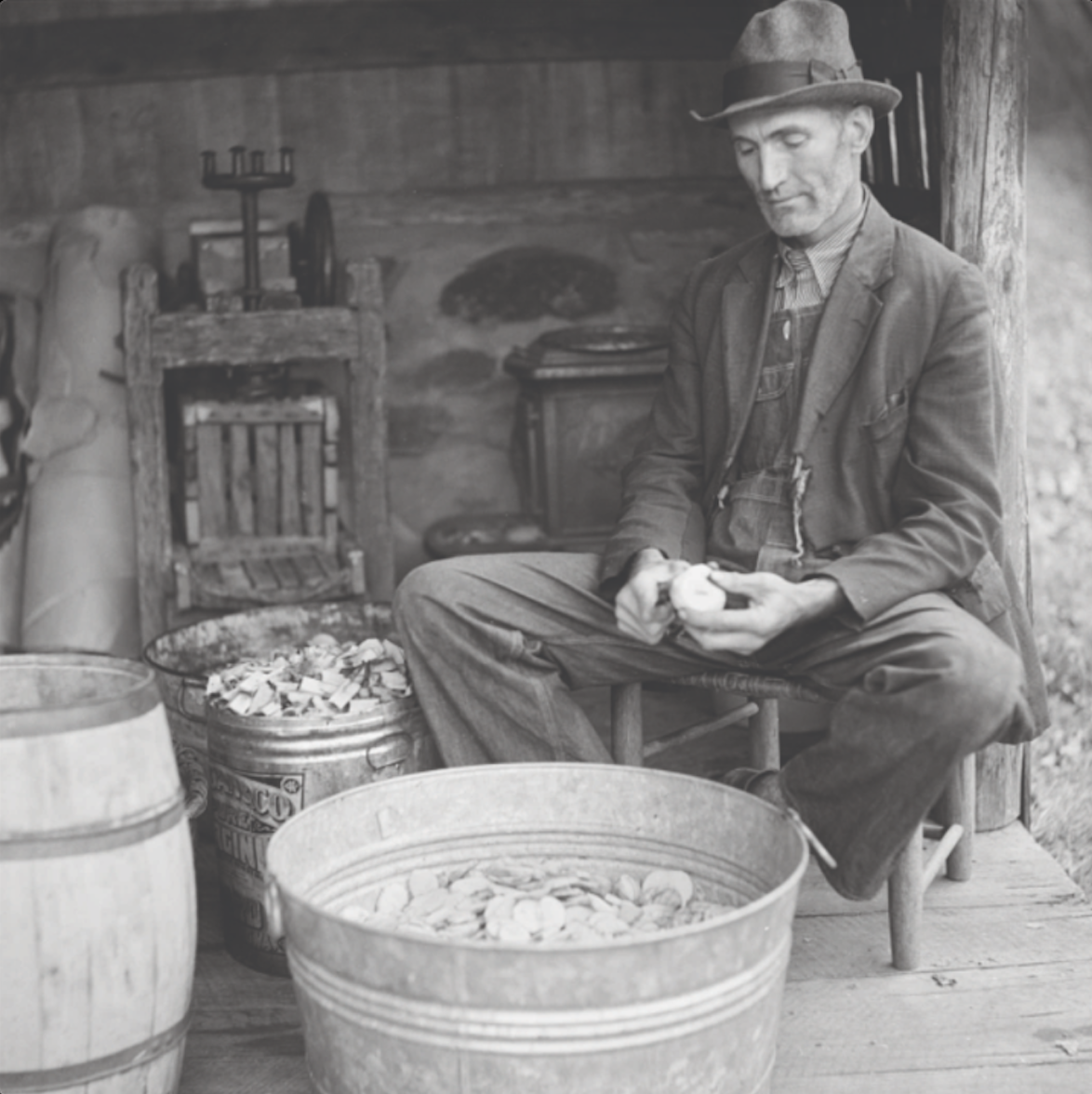 vintage photograph of a man in a coat and hat peeling apples