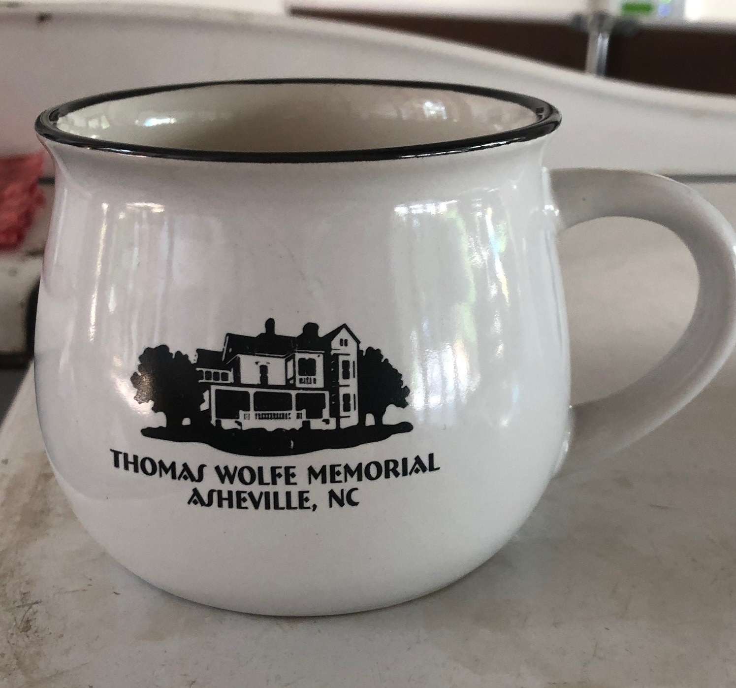 White coffee mug with image of the Old Kentucky Home in black and the words Thomas Wolfe Memorial Asheville NC