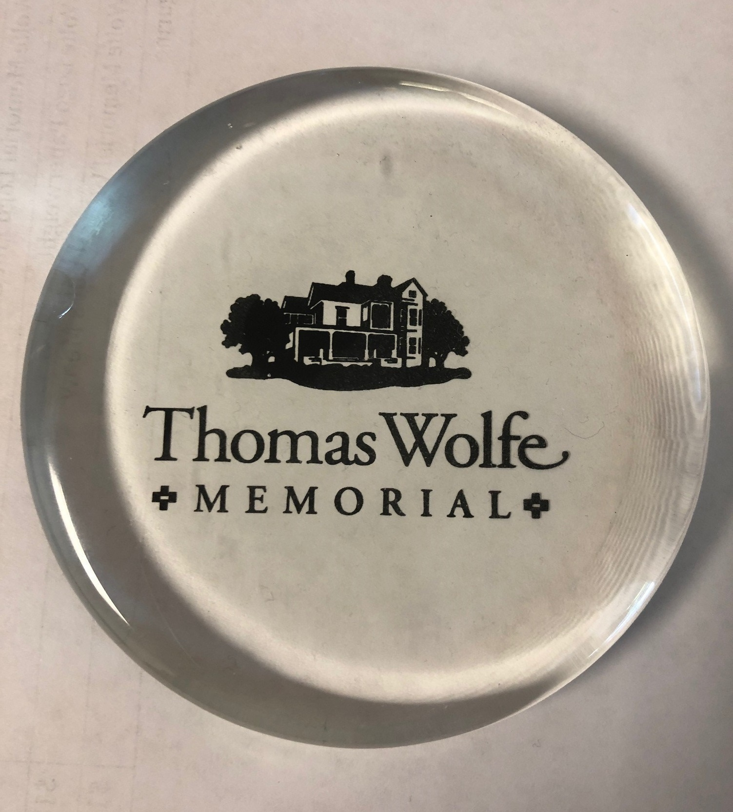 Clear round disc shaped paperweight with the Old Kentucky Home in black and the words Thomas Wolfe Memorial