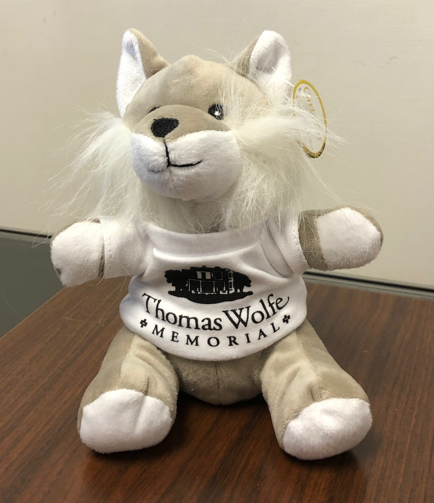 A plush animal of a wolfe wearing a white shirt with the Old Kentucky Home in black and the words Thomas Wolfe Memorial