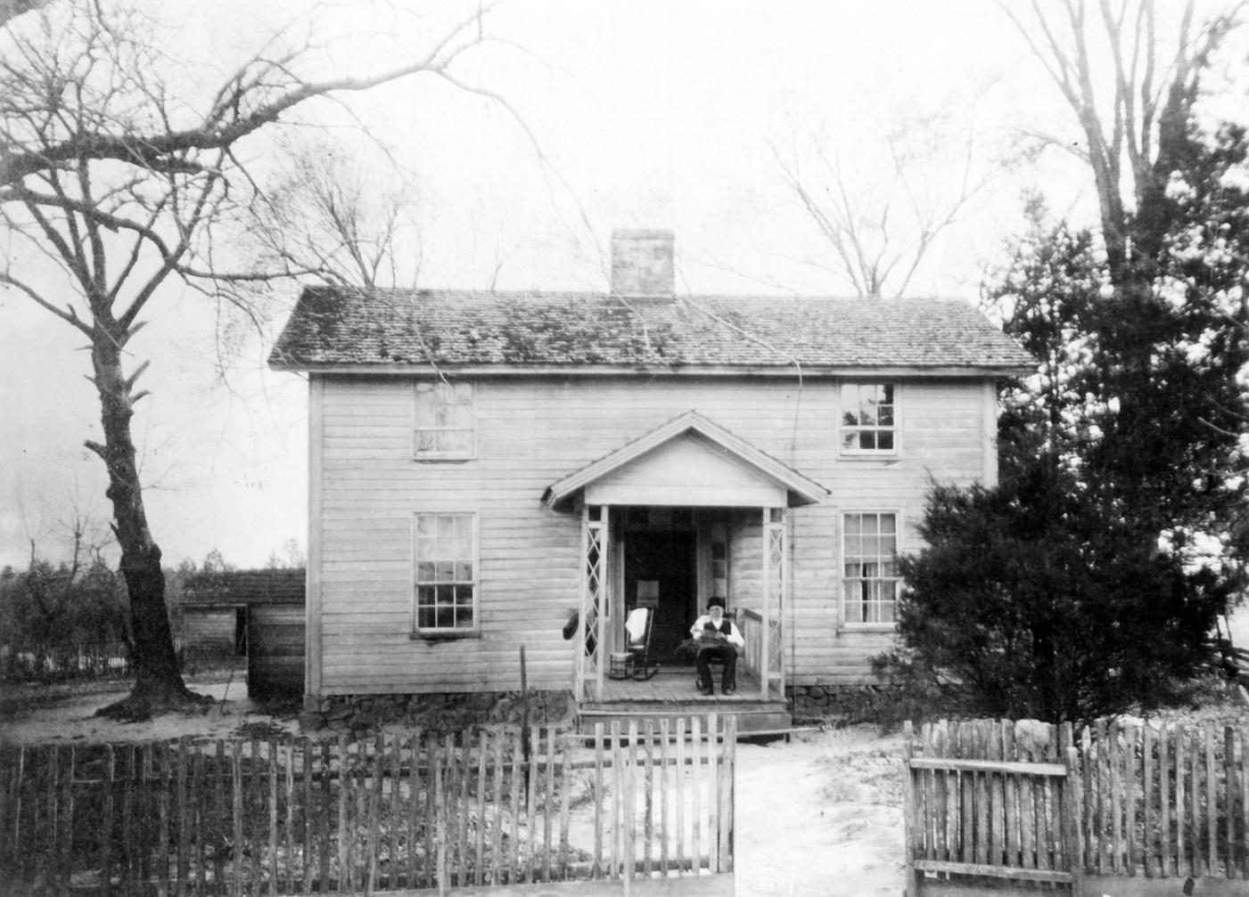 Washington Duke seated on the front porch of Duke Homestead farmhouse