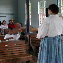 Reenactor speaks to children inside one room schoolhouse at Aycock Birthplace