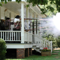 Men shooting from porch of the Alston House at a reenactment