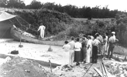 Joffre Lanning Coe speaks to some visitors of the archaeological excavation