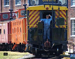 man stands in doorway of train car at the NC Transportation Museum