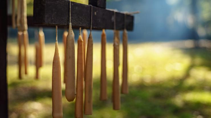 Hand-dipped candles drying on a wooden rack