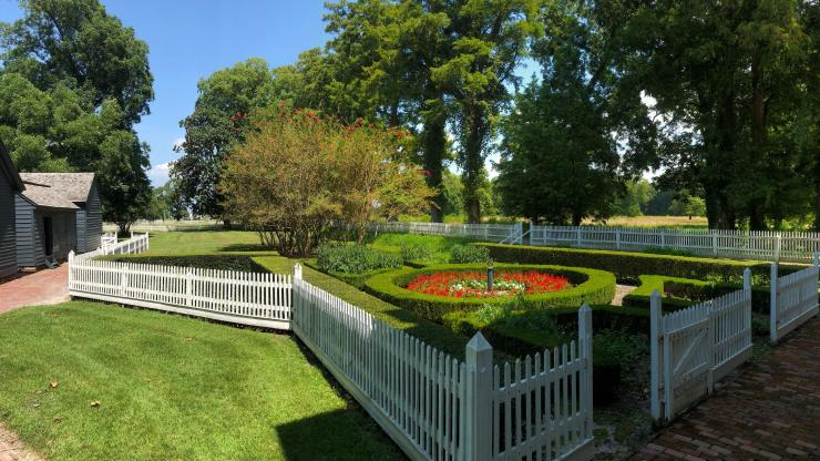 formal garden surrounded by white fence
