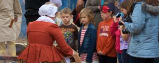 an interpreter speaks to a group of children