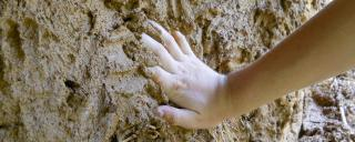 child's hand daubing mud on wall