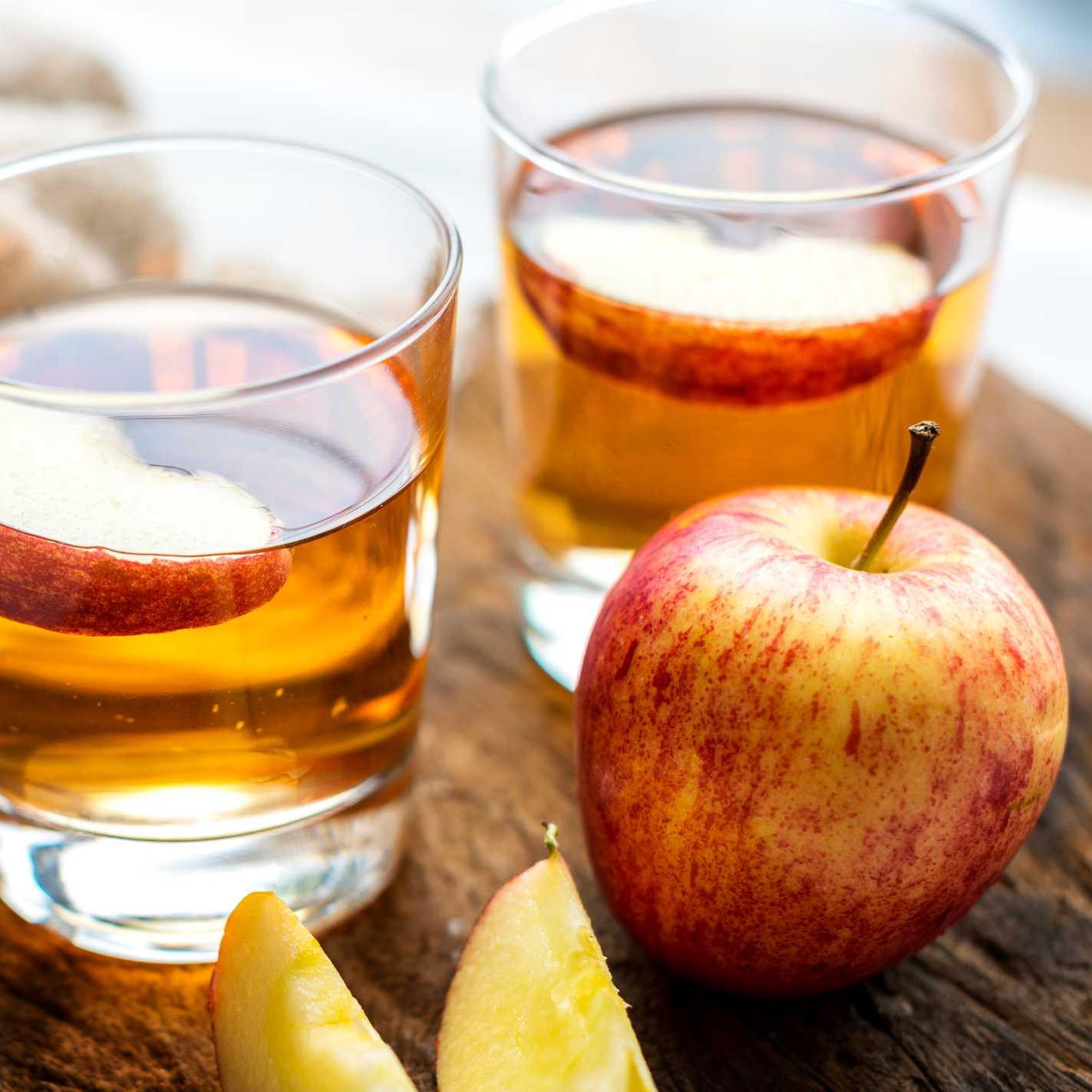 two glasses half filled with an amber liquid with apple slices floating on top. A yellow and red striped apple is near the glasses