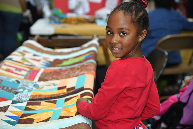 a young African American girl smiles with a colorful quilt behind her