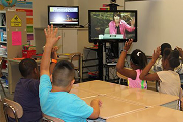 "Students watching a ""Distance Learning"" video in their classroom"