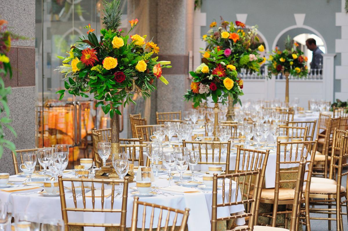 Bouquets of flowers lining tables in the lobby of the North Carolina Museum of History during a private dinner