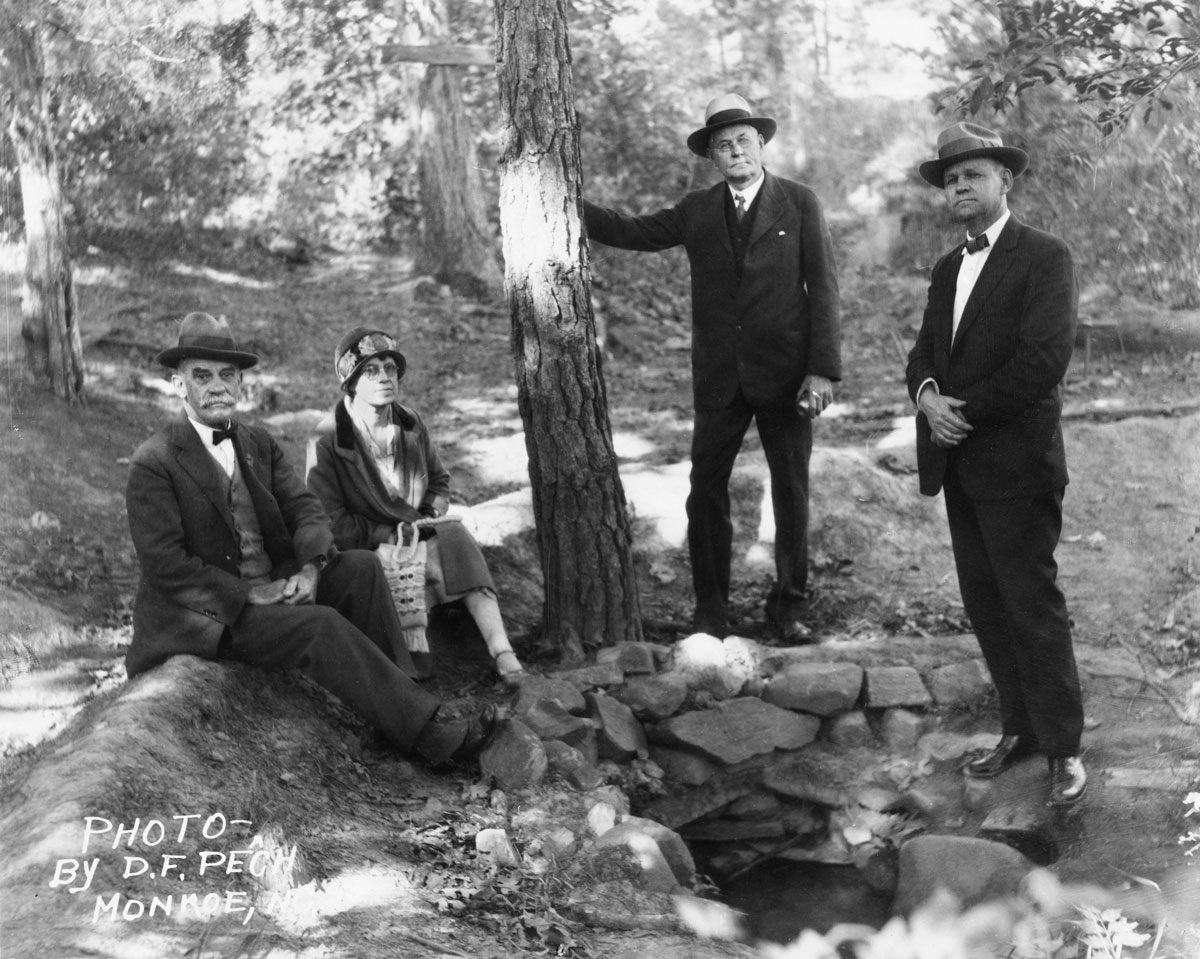 A black-and-white photograph of Frederick Augustus Olds, the North Carolina Museum of History founder, alongside two men and a woman by a tree