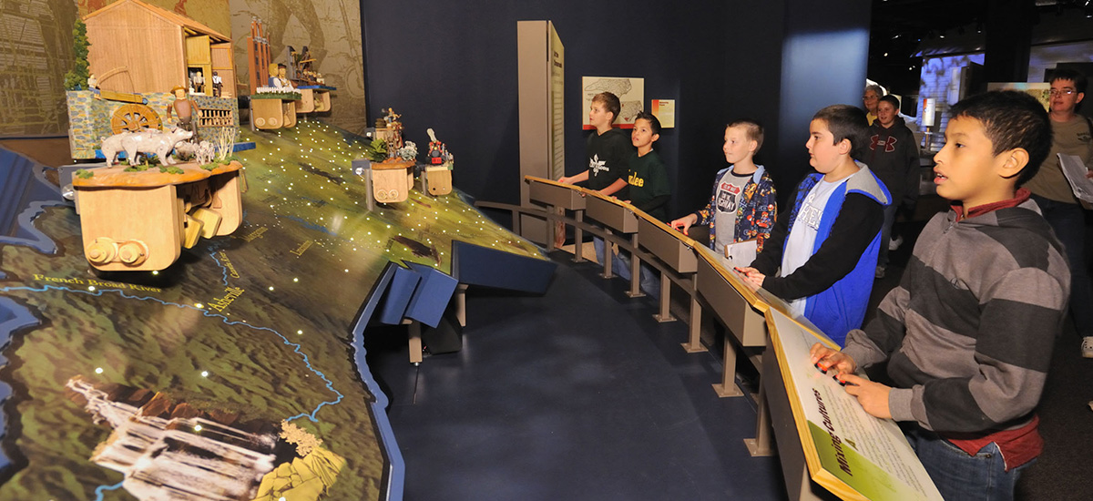 "Five children exploring the exhibit, ""The Story of North Carolina."""