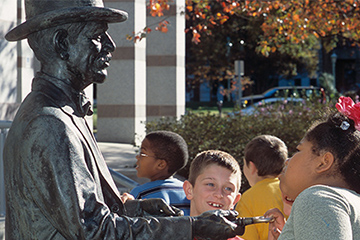 Children looking at the statue of Fred Olds, the North Carolina Museum of History founder