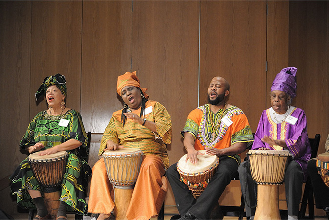 Three African American Women and One African American Man playing the drums