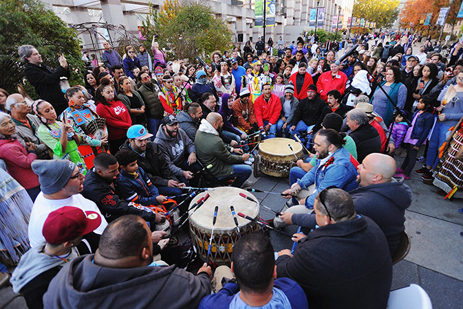A giant drum circle, featuring American Indian men, takes places in a large crowd