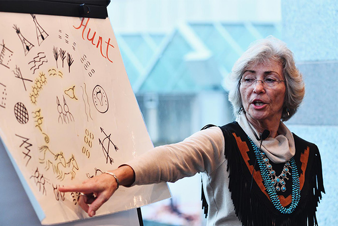 Gwen Locklear, a member of the Lumbee tribe, shares a story using a board