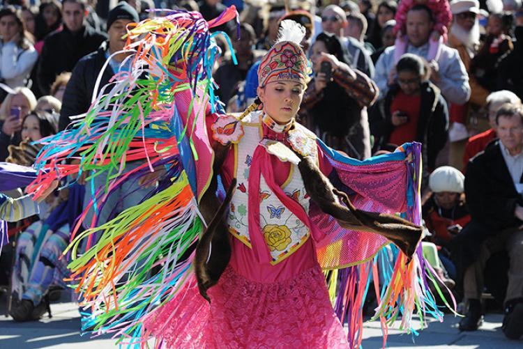 a young American Indian woman dances in a large crowd, wearing pink regalia