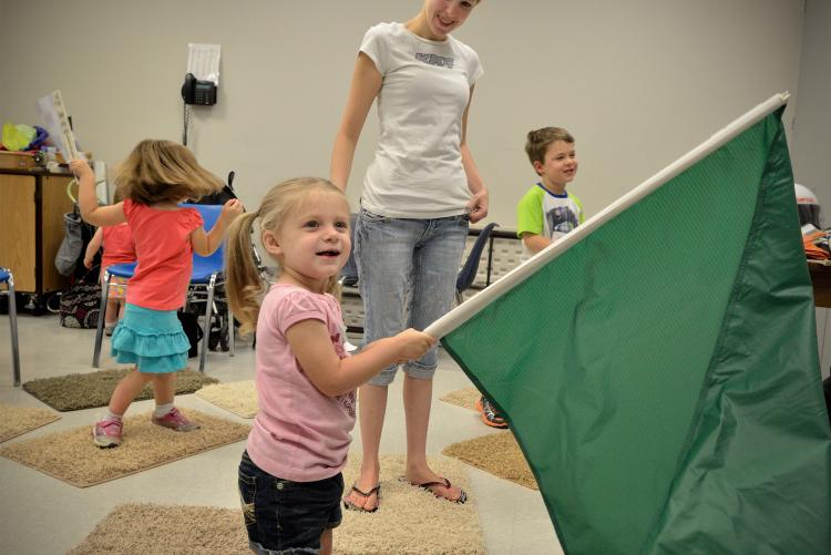 Blonde girl holding racing flag at North Carolina Museum of History
