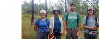 four interns stand facing the camera in a pine savanna