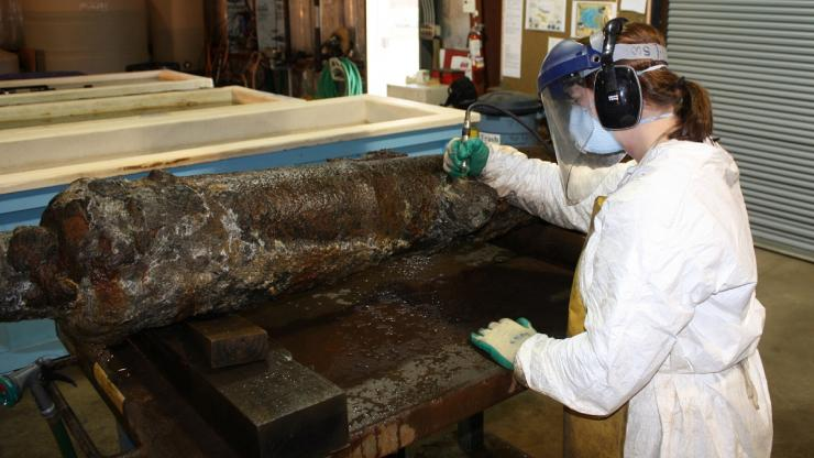 A researcher examines a cannon retrieved from the Queen Anne's Revenge wreck site.