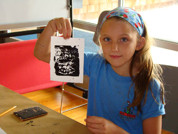Girl showing brass rubbing art at 16th century Saturday program at Roanoke Island Festival Park