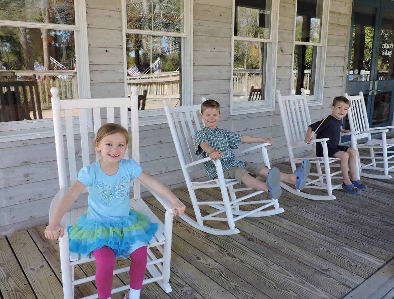 3 kids in rockers on the front porch of Roanoke Island Festival Park