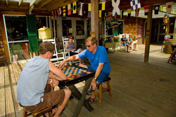 Father and son playing Elizabethan games on the porch at Roanoke Island Festival Park