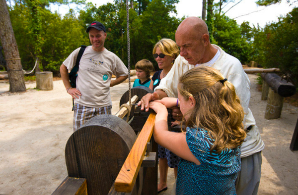 Historic interpreter showing family how to use the shaving horse at the Settlement Site at Roanoke Island Festival Park