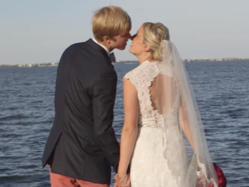 Groom and bride kissing and hold hands on pier at Roanoke Island Festival Park
