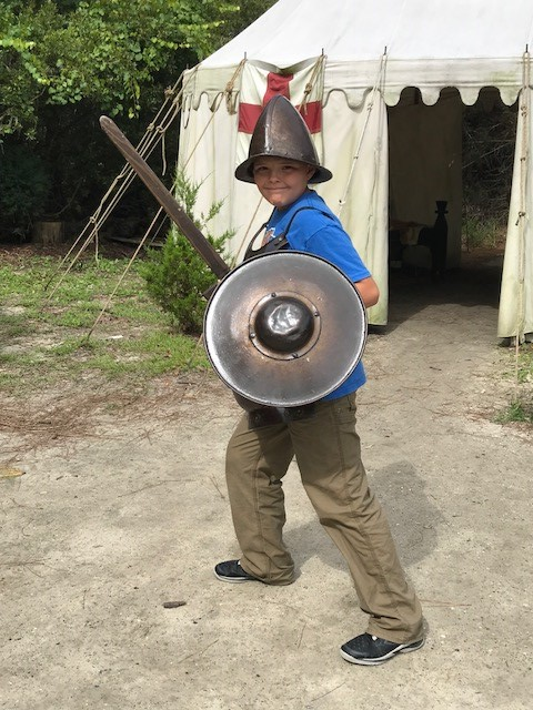 Boy dressed up in military gear in the Settlement Site at Roanoke Island Festival Park