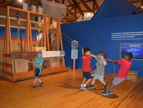 Kids playing with pulley exhibit in Adventure Museum