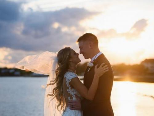 Bride and groom, Kaitlin and Taylor, sunset wedding photo on the pier at Roanoke Island Festival Park