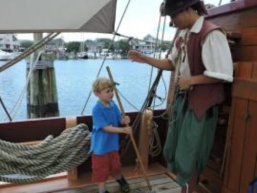 Boy swabbing the deck of the Elizabeth II with a sailor at Roanoke Island Festival Park
