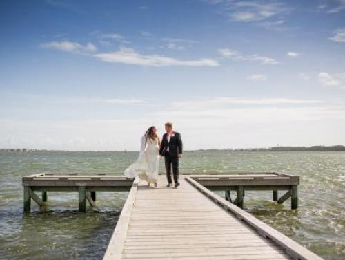 Bride and groom walking on the pier during their wedding at Roanoke Island Festival Park