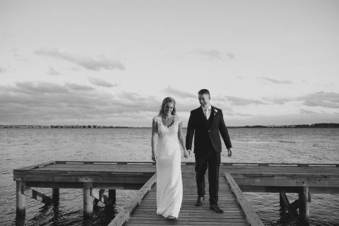 Bride and groom holding hands on the pier at Roanoke Island Festival Park