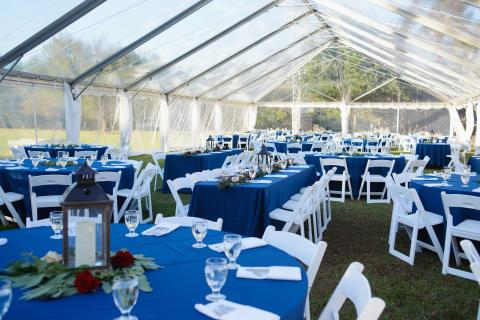 Wedding reception tables inside a tent at Roanoke Island Festival park