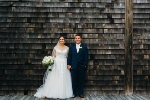 Bride and groom in front of cedar shake wall at Roanoke Island Festival Park