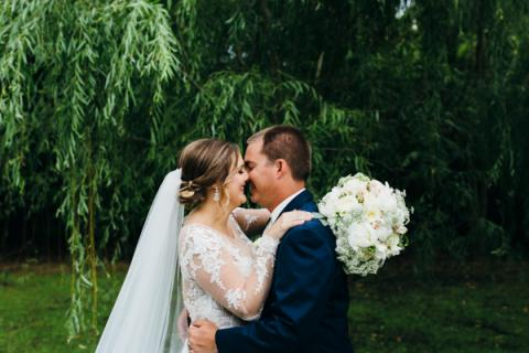 Bride and groom kissing under the trees at Roanoke Island Festival Park